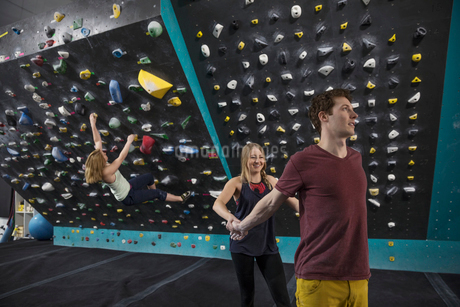 Rock climbers helping each other stretch, preparing at climbing gymの写真素材 [FYI02328279]