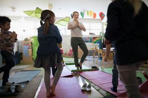 Preschool teacher and students practicing yoga tree pose in classroomの写真素材 [FYI02328362]