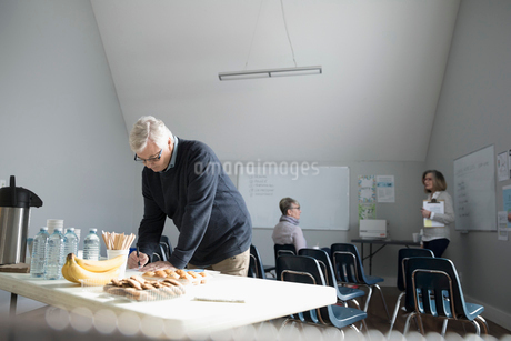 Man filling out paperwork at support group in community centerの写真素材 [FYI02328407]