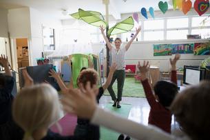 Preschool teacher and students practicing yoga tree pose in classroomの写真素材 [FYI02328421]