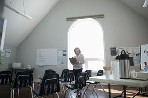 Woman with clipboard preparing for meeting in community centerの写真素材 [FYI02328439]