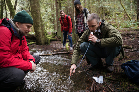 Trail guide and family drinking from stream in woods, using pump filterの写真素材 [FYI02328484]