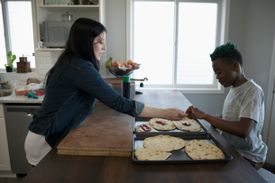 Mother and and son making homemade pizzas in kitchenの写真素材 [FYI02328505]