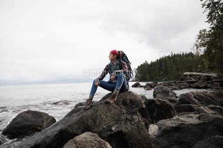 Thoughtful female hiker sitting on rocks on rugged beachの写真素材 [FYI02328579]