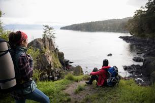 Female backpackers resting, enjoying ocean viewの写真素材 [FYI02328612]