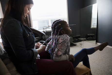 Mother braiding multicolor string in daughterの写真素材 [FYI02328651]