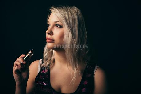 Renaissance portrait thoughtful female millennial using vape penの写真素材 [FYI02328666]