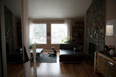 Boy reading book on living room rugの写真素材 [FYI02328694]