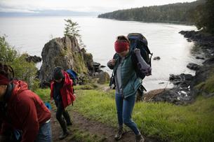 Friends backpacking on cliff overlooking oceanの写真素材 [FYI02328717]