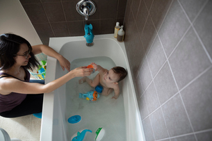 Mother bathing baby son taking bath, playing with toys in bathtubの写真素材 [FYI02328834]