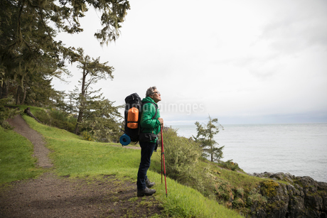 Active senior man backpacking on cliff overlooking oceanの写真素材 [FYI02328845]