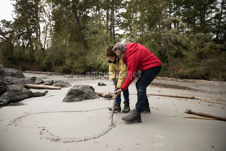 Affectionate active senior couple drawing heart-shape in wet sand on rugged beachの写真素材 [FYI02328913]