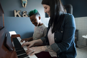 Mother teaching son piano lessonの写真素材 [FYI02328921]