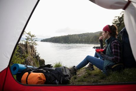 Woman eating, camping on cliff overlooking oceanの写真素材 [FYI02328927]