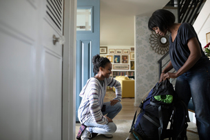 Mother helping teenage daughter prepare travel backpackの写真素材 [FYI02328980]