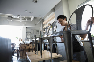 Young woman small business owner stacking chairs on tables in cafeの写真素材 [FYI02329052]