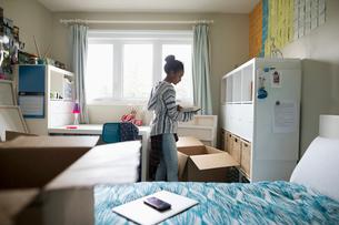 Teenage girl packing bedroom, preparing for collegeの写真素材 [FYI02329054]