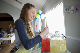 Smiling girl preparing lemonade and strawberry lemonade at bake sale in community centerの写真素材 [FYI02329065]