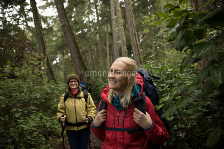 Smiling, carefree active senior women hikers hiking in woodsの写真素材 [FYI02329068]