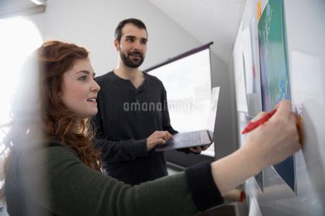 Creative designers editing poster on whiteboardの写真素材 [FYI02329081]