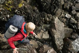 Active senior woman backpacking, descending craggy rocksの写真素材 [FYI02329103]