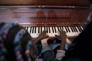 Overhead view mother teaching daughter piano lessonの写真素材 [FYI02329143]
