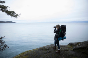 Woman backpacking, using digital camera to photograph scenic ocean viewの写真素材 [FYI02329194]