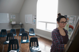 Woman at whiteboard preparing for support group in community centerの写真素材 [FYI02329201]