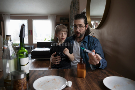 Father giving son medicine at dining tableの写真素材 [FYI02329207]