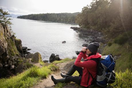 Female backpacker using binoculars, enjoying ocean viewの写真素材 [FYI02329208]