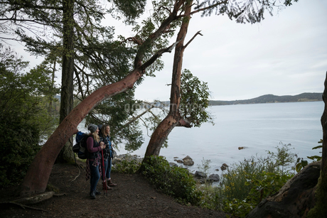 Mother and daughter backpacking along oceanの写真素材 [FYI02329223]