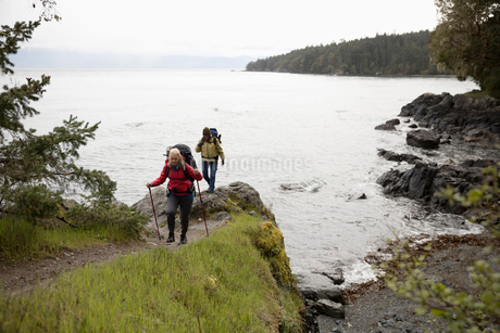 Active senior women friends backpacking on cliff trail overlooking oceanの写真素材 [FYI02329269]