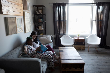 Affectionate mother and son reading book on sofaの写真素材 [FYI02329397]