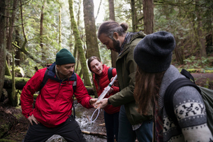 Trail guide showing family how to use pump filter in woodsの写真素材 [FYI02329430]
