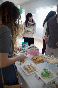 Women buying and selling desserts at bake sale in community centerの写真素材 [FYI02329446]