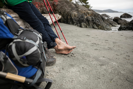 Barefoot man backpacking, resting on rugged beachの写真素材 [FYI02329455]