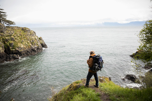 Active senior man backpacking on cliff with scenic ocean viewの写真素材 [FYI02329501]