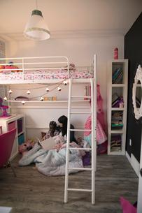 Mother reading bedtime story book to daughter in bedroomの写真素材 [FYI02329534]