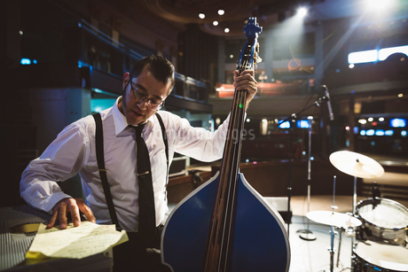 Musician with double bass preparing, reviewing stage setの写真素材 [FYI02329592]