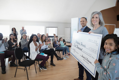 Portrait smiling community clapping, presenting large donation checkの写真素材 [FYI02329629]