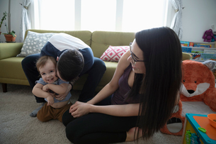 Playful young family in living roomの写真素材 [FYI02329644]