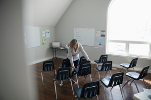Woman unstacking, arranging chairs for meeting in community centerの写真素材 [FYI02329661]