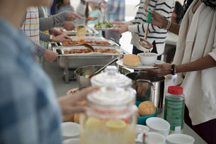 People serving food at soup kitchen community dinnerの写真素材 [FYI02329667]