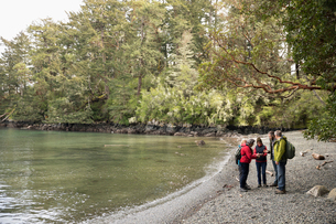 Active senior friends hiking along lake in woodsの写真素材 [FYI02329669]
