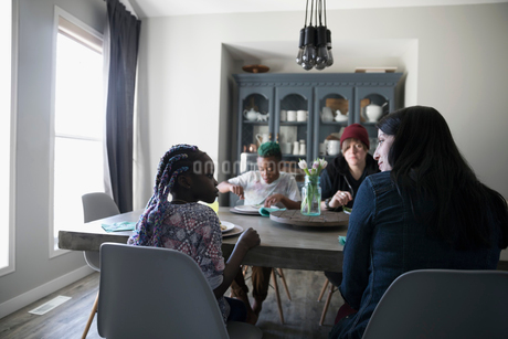Homosexual couple and children eating at dining tableの写真素材 [FYI02329728]