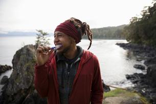 Happy male backpacker brushing teeth on cliff overlooking oceanの写真素材 [FYI02329784]