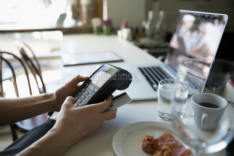Businesswoman paying, using credit card reader in cafeの写真素材 [FYI02329792]