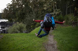Playful male backpacker jumping for joy on trail in woodsの写真素材 [FYI02329846]