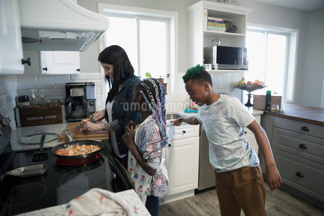 Mother and children preparing and cooking vegetables at kitchen stoveの写真素材 [FYI02329870]