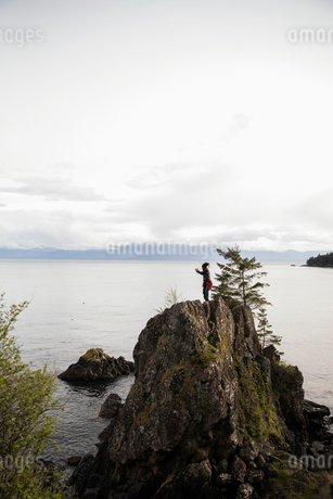 Male backpacker standing on rock cliff overlooking oceanの写真素材 [FYI02329919]